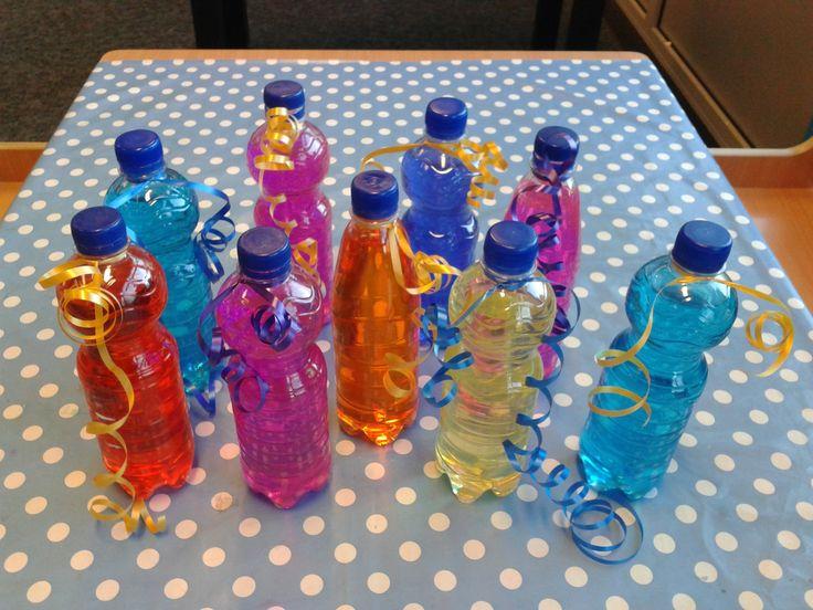 """Licht gevende gekleurde glitter fles maken thema: oud en nieuwjaar. Vul de fles met water, en hang er crêpepapier in tot het water een mooie kleur heeft. Doe er wat glitters in en een """"glow in the dark"""" breekstaafje voor het licht. (het staafje niet open knippen!) Draai de dop er op en versier de buitenkant van de fles met bijv. stickertjes. In het donker geeft de fles mooi licht door het breekstaafje en de mooie glitters zijn goed te zien. Kinderen vinden het geweldig!"""