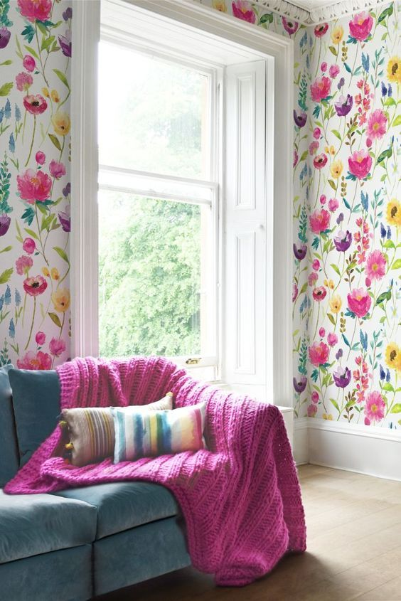 Colorful floral print wallpaper in the living room and a matching knit fuchsia blanket