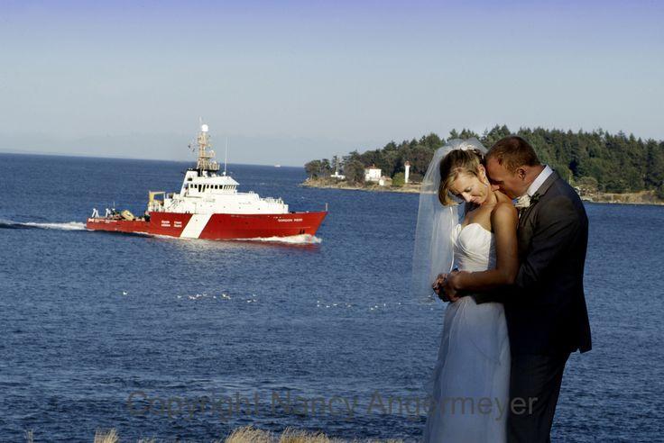 wedding couple on galiano island with coast guard ship passing by.
