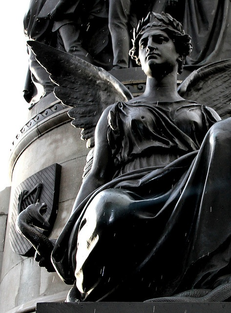 Monument to Daniel O'Connell in O'Connell Street, Dublin. Holding a snake, she symbolises O'Connell's courage. Bullethole in her breast is from the 1916 Easter Rising.