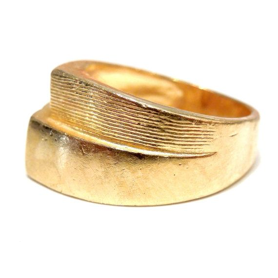 This 21k yellow gold ring has a nice, retro design. Half of the face of the ring is textured with a handsome pattern of carved thin horizontal lines, while the other half is completely smooth.  The inside of the ring is stamped 9999 (meaning 99.99% pure gold), however, we have had it assayed and its purity is 21K (87.5%).  SIZE 7.5 (can be sized)