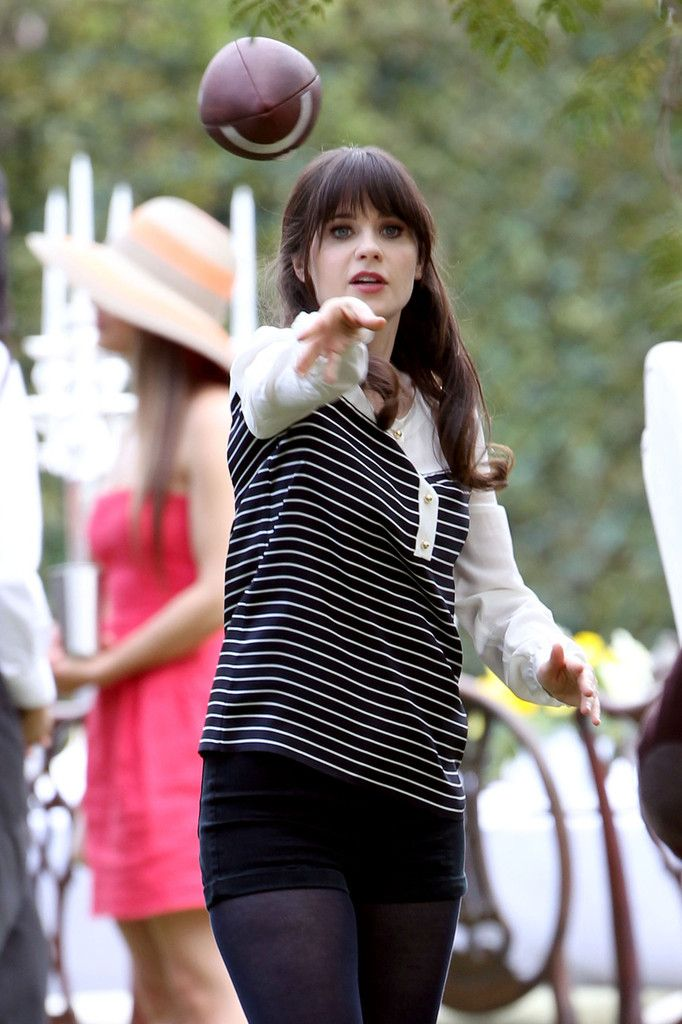 Zooey Deschanel Photos Photos - Zooey Deschanel shows off her football skills while playing a game of catch with co-star Steve Howey (of 'Shameless' fame) on the set of 'New Girl.' Zooey had a minor wardrobe malfunction as her shirt became unbuttoned and exposed her bra to crew members, which she quickly buttoned up. Also spotted on set was Jake Johnson showing off football skills between takes. - Zooey Deschanel Plays Football on Set