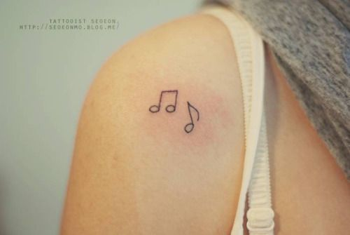 Minimalistic music note tattoos on the right shoulder. Tattoo...