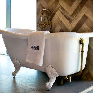 Nostalgische maatwerk badkamer met bronzen details. Het vrijstaand bad op leeuwenpoten heeft een bronzen afvoer aan de buitenkant en een bijpassende bronzen afvoer. Daarnaast is het bad voorzien van een stop- en handdouche met telefoonhaak. De granieten wasbakken steken mooi af tegen de decor tegels die gelegd zijn in een visgraat patroon. Daarnaast passen ook de getinte douchewand en bronzen regendouche goed in de badkamer met vintage look / #design_badkamers_breda