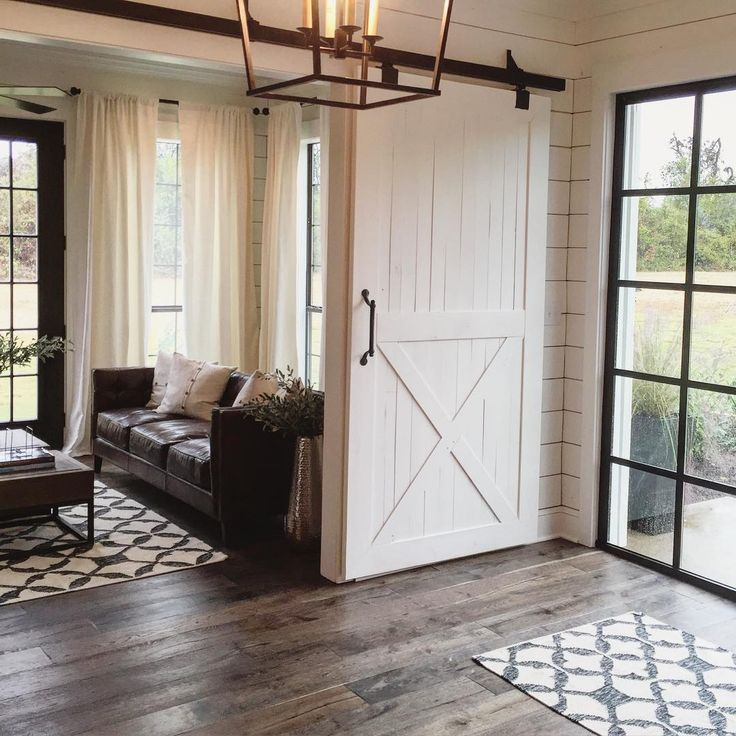 Dark wood flooring & sofa, chic sliding door, beautiful panel windows and patterned rugs.