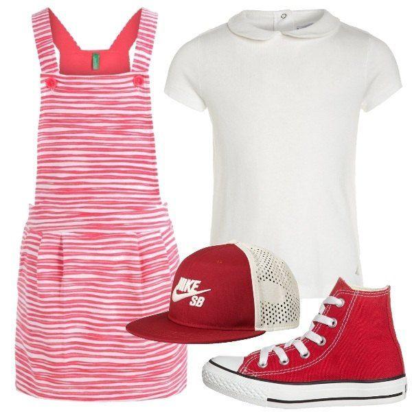 T-shirt bianca in cotone con colletto peter pan abbinata a salopette a righe rosse e bianche. Completano il look le sneakers alte Converse rosse e il cappellino con visiera.