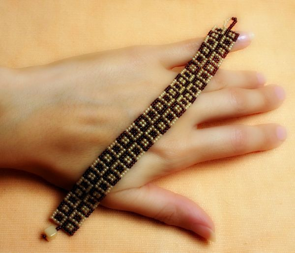 "I hand wove this unique bracelet in herringbone technique using seed beads # 11 in two colors (brown and beige). The closure is a beaded loop with a square bead. It measures 7""..."