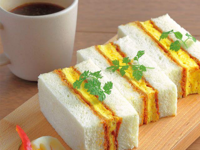 《 渋谷 》『GRAIN BREAD AND BREW』の  「オムレツカツサンド、ホースラディッシュソース仕上げ」¥918  たまごをカツにした、ありそうでなかった味わいが人気のサンド。メゾンカイザー製のパンに塗られた2種のソースがカツの旨みを引き立てる。  バゲット、ピタ、チャバッタなど具材に合わせた5種類のパンを使用したオリジナルメニューが評判の、クラフトサンドウィッチ専門店。氷川神社すぐそばという隠れ家的立地もあり、オリジナルサンドとこだわりのスペシャルティコーヒーを落ち着いた雰囲気で楽しめる。近隣のビジネスマンを中心に人気を集めている。