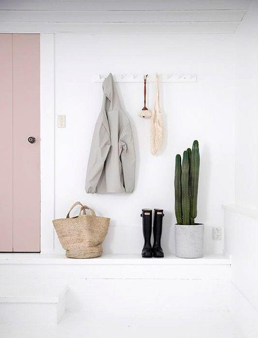pink door in white entryway with wall storage rack. / sfgirlbybay