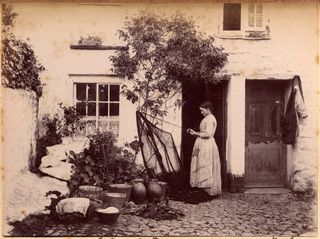 A photograph of a woman beating a fishing net outside a white granite house in Newlyn. The net is laid out on the base of a climber. Other plants, including nasturtiums, grow in pots in front of the wall. A number of pails, bowls, pitchers and bussas sit on the cobbled lane, indicating that it was the centre of much activity. A coat hangs on a hook in the doorway next door. - Collections - Penlee House Gallery and Museum Penzance Cornwall UK