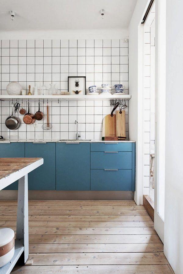 Cuisine esprit rétro avec meubles de cuisine bleus. Le parquet apporte une bonne dose de chaleur. La crédence avec un carrelage carreaux joints noirs complète le décor.