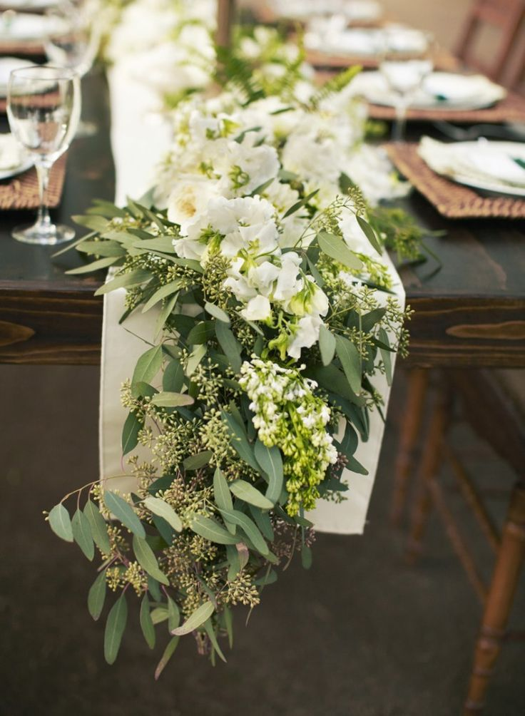 The guest book table at the church will have a runner of pillar candles in vases at varied heights, green seeded eucalyptus, gray dusty miller, magnolia leaves, and white stock flowers.