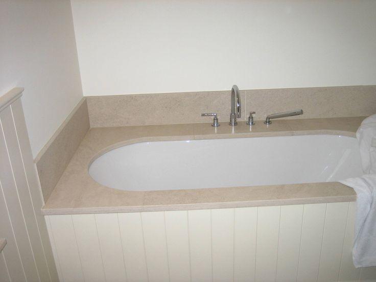 Onderbouw bad afgewerkt met natuursteen en lambrisering met groef. Landelijke stijl. Kraanwerk Dornbracht.