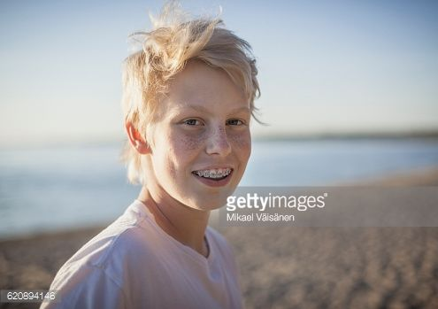 Stock Photo : Portrait of teenage boy with braces on the beach