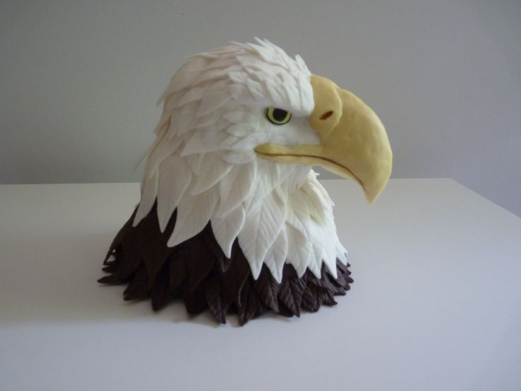 Eagle Cake ~ The head is made of RCTs covered in chocolate candy clay feathers.  I made the beak with RCTs and attached using dowel rods, covered it in yellow candy clay.  Eyes made of fondant.