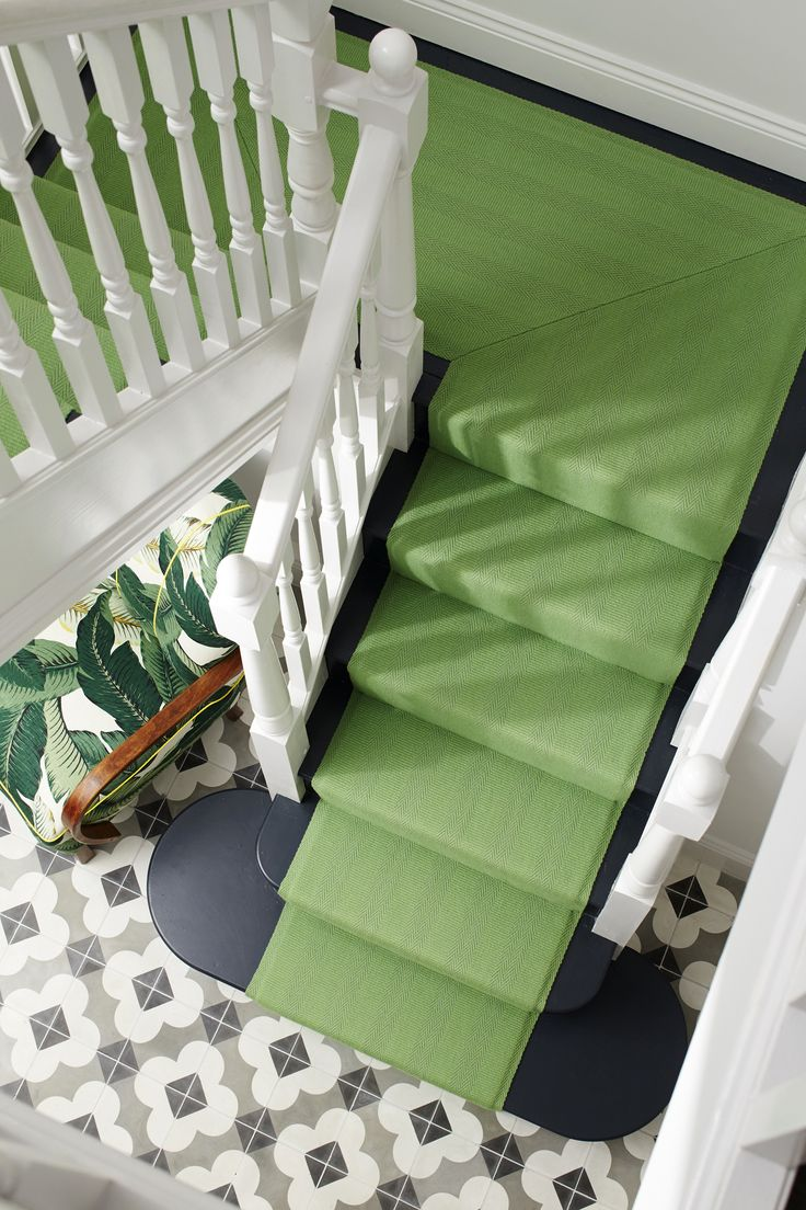 Tiles, green stair runner and banana palm chair in the hallway of Erica Davies from the-edited.com (image: Christopher Cornwell for Roger Oates)