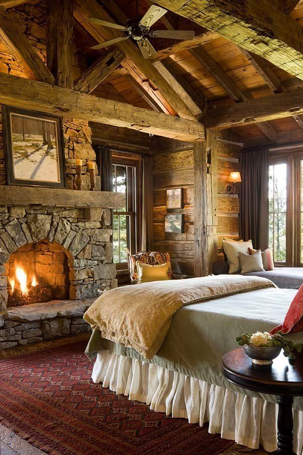 Bedroom fire place with log and chink construction and hand hewn beams