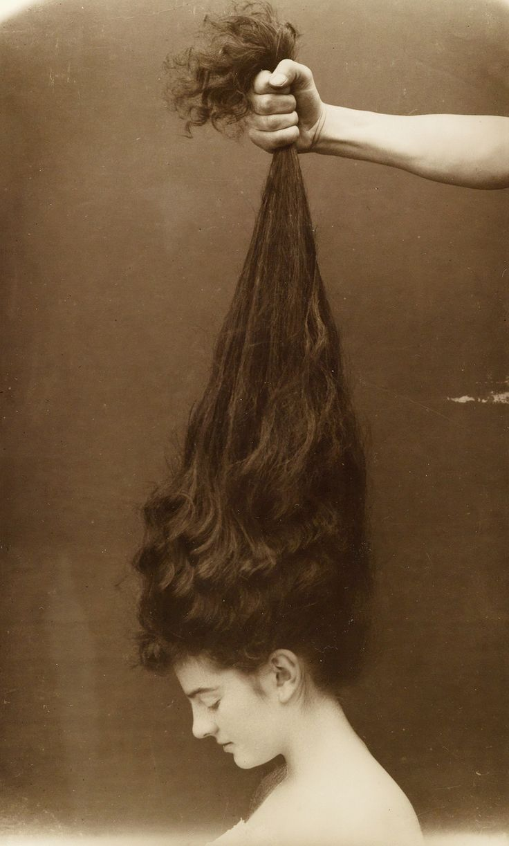 Hand grasping a young woman's long, dark hair. Photographer Unknown ca.1910