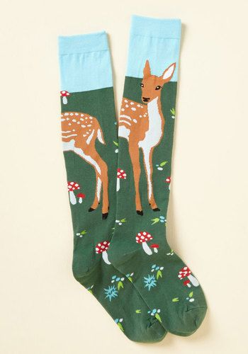It takes you a moment, but then you realize - the snuggliest part of your morning is the moment you pull on these green knee socks! Knit with the design of a young deer in a meadow of grass and mushrooms, this tan, red, and sky blue pair brings comfy revelations to your ensemble.