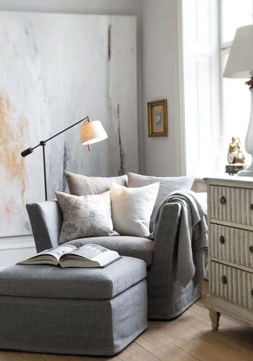 Let your large art do all of the talking and keep the rest of the decor simple when it comes to creating a relaxing reading nook in your home. In this gorgeous space, bold oversized artwork pairs well with a cushy armchair and classic white dresser.