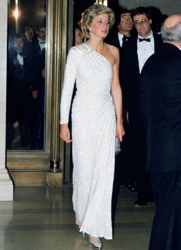 Los vestidos más icónicos de Diana de Gales - Uno de los primeros guiños de Diana a la elegancia que convertiría en su sello personal fue este espectacular vestido-joya de color blanco, con escote asimétrico, que combinó con zapatos y bolso de mano en plata.