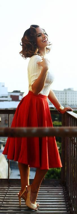 White knit top with red tea length skirt.