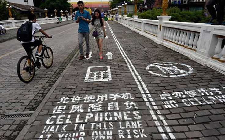 Estamos locos?? División peatonal en dos partes, que separa a los transeúntes que andan con smartphone para evitar los accidentes que esta situación provoca