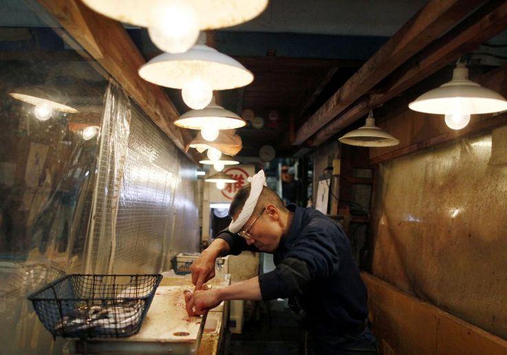 Ένας Ιάπωνας τεχνίτης τεμαχισμού του τόνου καθαρίζει τα ψάρια στην ψαραγορά χονδρικής Τσουκίτζι στο Τόκιο.