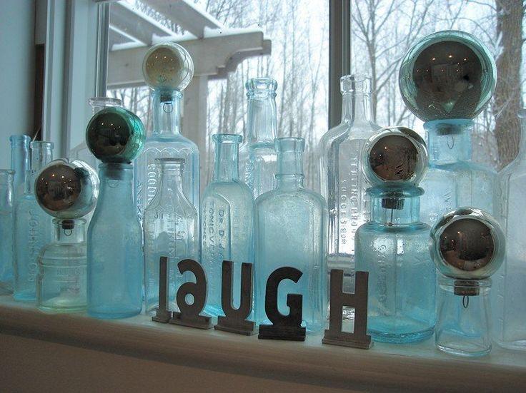 Glasflaschen und kopf gestellte Glaskugeln auf der Fensterbank