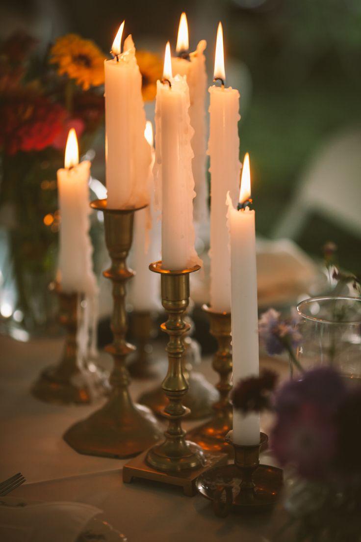 Candles and antique brass candlesticks at wedding reception.  Read More: http://www.stylemepretty.com/2014/07/23/heartwarming-garden-wedding/