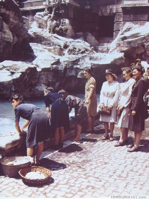 Italian women wash clothes at the fountain of Fontana Verdi while US Army nurses and GI's look on. June 1944