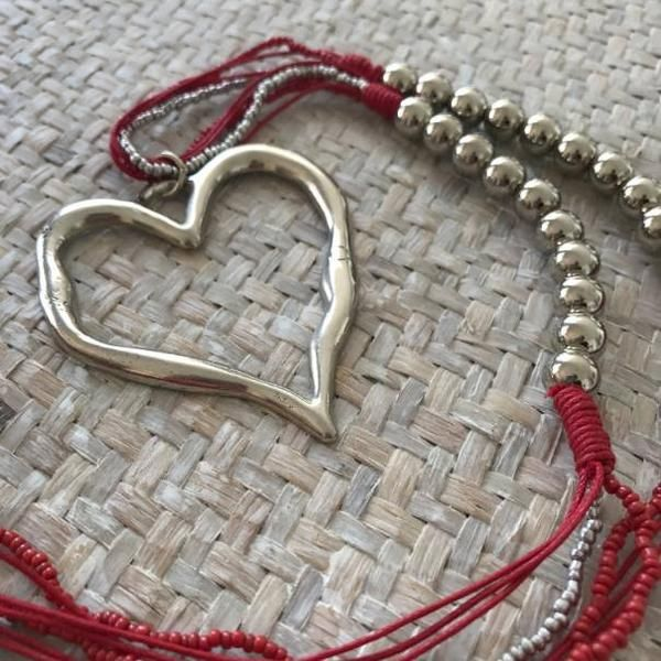 Beautiful silver heart pendant necklace featuring a trendy open heart pendant suspended from an amazing necklace of silver beads, coloured seed beads, coloured thread and tiny silver beads.   Available in a rich red and a calm sky blue.