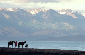 Horseback riders pause for a breath-taking view of the Kenai Mountains from a spit near Homer, Alaska