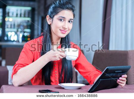 Young indian businesswoman on a coffee break. Using tablet computer.