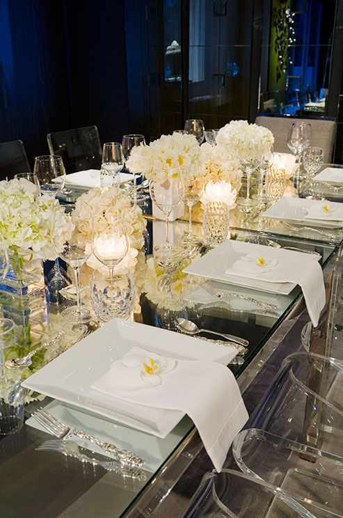 wedding tables: When paired with sultry blue lighting, light blooms with glass and crystal place settings illuminate the dining table.
