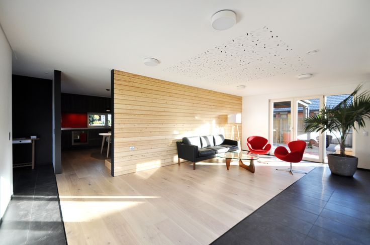 10 Star living room with Gib acoustic ceiling lining and feature wall lined with European Larch, black tile help absorb solar gain into the thermal mass of the fully insulated concrete slab