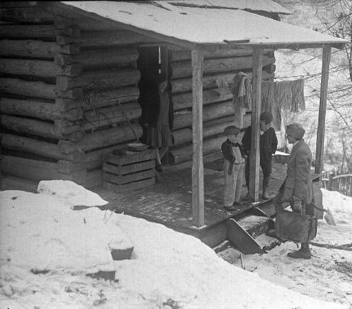 1933: Nurse Mary B. Willeford from Frontier Nursing Service, visits patients: a woman and two young boys on log cabin porch, The woman is in the doorway and the boys are on the porch at the top of the steps with their hands in their pockets. There is light snow on the ground and roof and a line of laundry on the porch. -Herald-Post Collection