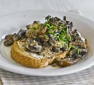 Creamy mustard mushrooms on toast with a glass of juice - A quick and healthy vegetarian breakfast with a light cream cheese sauce