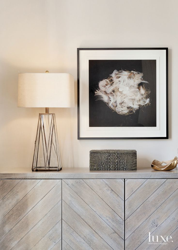 In the living room, the designer topped a chevron-patterned chest by Bradley with a metal-and-glass lamp and crocodile-embossed porcelain box, both purchased from Anthem. The photograph hanging above is 'Bank Swallow' by Sharon Beals.