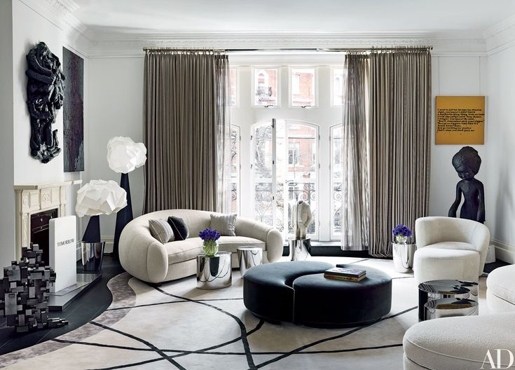 In the living room of a London townhouse by François Catroux, a Jean Royère sofa (left) and a Vladimir Kagan sofa, lounge chair, and ottoman (all clad in sheepskin) mingle with Mauro Fabbro lamps from Alexandre Biaggi and a pair of custom-made interlocking ottomans; the rug is by Tai Ping.