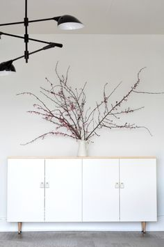 """DIY MODERN WHITE AND NATURAL WOOD BUFFET  This was so quick and easy!   Grab two 36"""" Ikea cabinets, some tapered wood legs, a wood top, leather and brass bolts for handles, and you're good to go.  Enormous branches optional."""