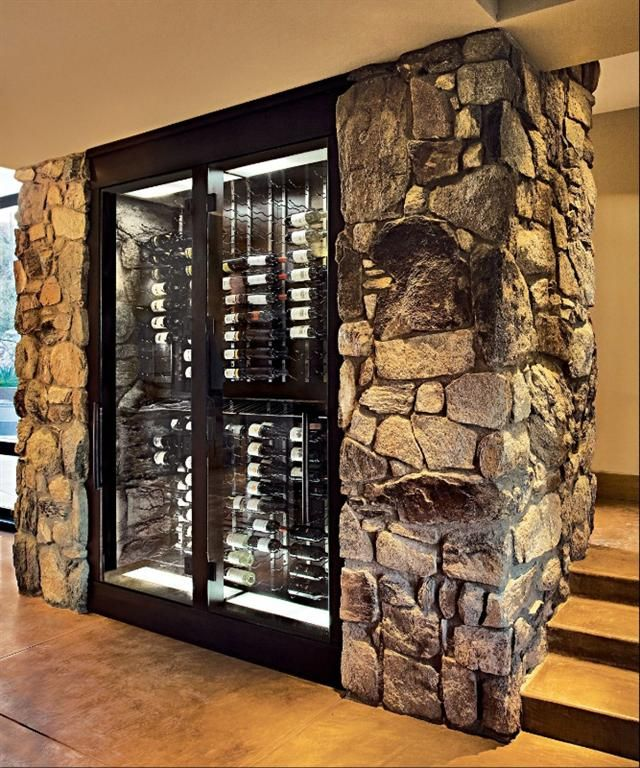 Architecture. Wine Cellar Design With Concrete Floor Material Plus Wall Bottle Shelves With Door Cover And Clear Glass Material Furthermore Natural Stone Wall.