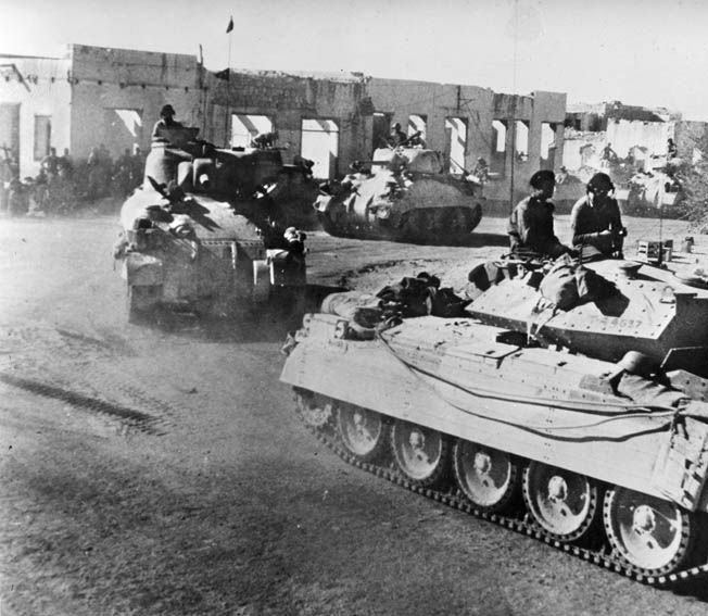 A British Crusader tank and a pair of American-built Sherman tanks churn through the ruins of a town in North Africa. British General Frank Messervy commanded the British 1st Armoured Division from the front and risked capture on more than one occasion.