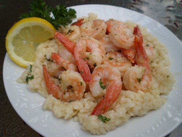Scampi With Risotto - CDKitchen.com -  Shrimp is cooked scampi style in a garlic and wine sauce and served over a simple risotto with parmesan cheese.