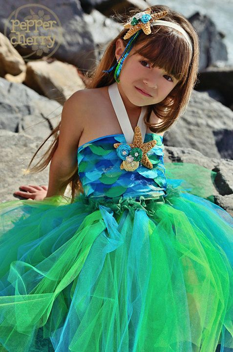 """Mermaid Tutu set is a three piece outfit which consists of a halter top bodice, tutu skirt, and detachable starfish clip. The top of the tutu dress is adorned with silky and sparkly """"scales"""" and the fin is created using various shades of green and blue tulle in our full tutu skirt....perfect for your little mermaid!"""