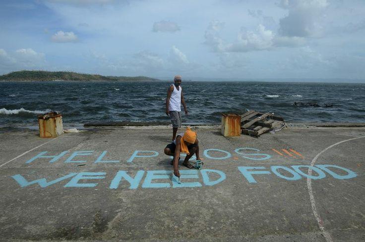Des hommes peignent «SOS, à l'aide, nous avons besoin de nourriture» sur un terrain de basket, à Anibong, à Tacloban, lundi.