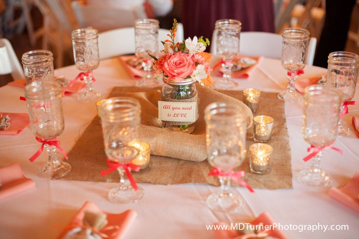 Burlap, mason jar and coral colored floral table setting