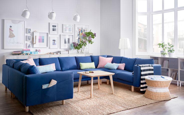 明るいリビングルームに大きなU字型の9人掛けのソファ。カバーはダークブルーのファブリック。アッシュ材突き板製のコーヒーテーブルと円形の籐のトレイテーブル、中に収納付き。