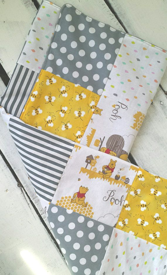 Baby blanket front is made of 100% cotton fabrics and has a patchwork design that features Winnie the Pooh, bumblebees, and polka dot prints in gray, yellow, and white shades. Backing fabric is ultra soft plush minky dot. Blanket measures 28x32 inches, which makes it perfect for use as a receiving blanket and for snuggling baby. ***THIS BLANKET IS READY TO SHIP! However, it is also available as a made to order quilt in the drop down menu. Allow an additional 4 days for production…