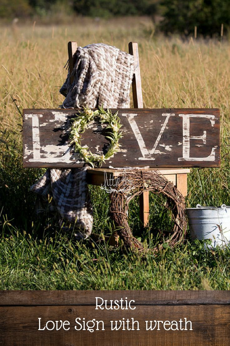Eye catching chippy LOVE sign made from old barn wood with a wreath. This would really look good on a white shiplap wall! #farmhouse #rustic #ad